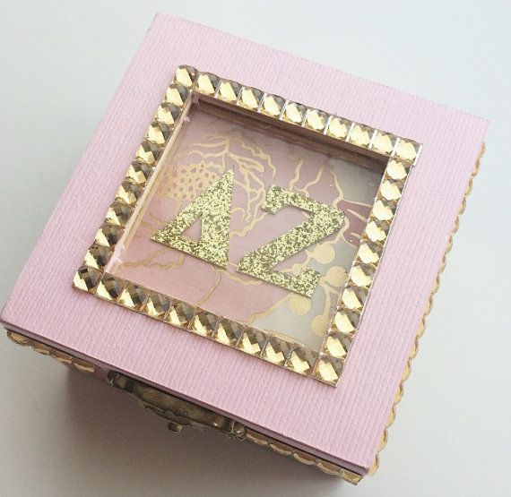 Handmade wooden jewelry/sorority pin box covered in a baby-pink, white and rose-gold metallic design. The letters are set underneath a sheet of glass and bordered by gold gems ***Initials or sorority letters will be altered upon order. 2.75 x 2.75 x 1.77.