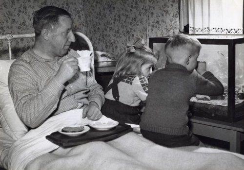 Vaderdag. Vader met ontbijt op bed. De kinderen zitten op de rand van zijn bed naar het aquarium te kijken. Bloemetjesbehang op de muur. Wit metalen bed. Meisje draagt rok met galgjes. Jaar en plaats onbekend.