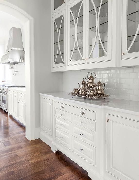 Gorgeous white butler's pantry boasts white cabinets accented with polished nickel hardware and a white marble countertop fixed against glossy white subway backsplash tiles positioned beneath glass mullion pantry cabinets.