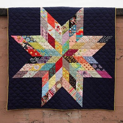 Jaime's Giant Star Quilt on a royal purple background. It is a traditional star quilt that has been magnified so each of its 8 points is made up of 9 different fabrics (72 fabrics altogether)