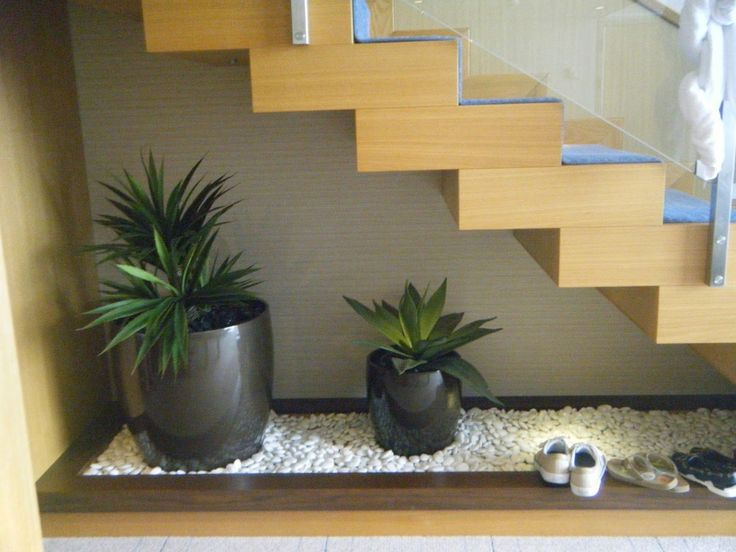 Interior , Adding Indoor Plants To Decorate Space Below The Staircase : Creative Pretty Green Plants In Black Planters Placed Under The Wooden Flowating Staircase With Rock Garden