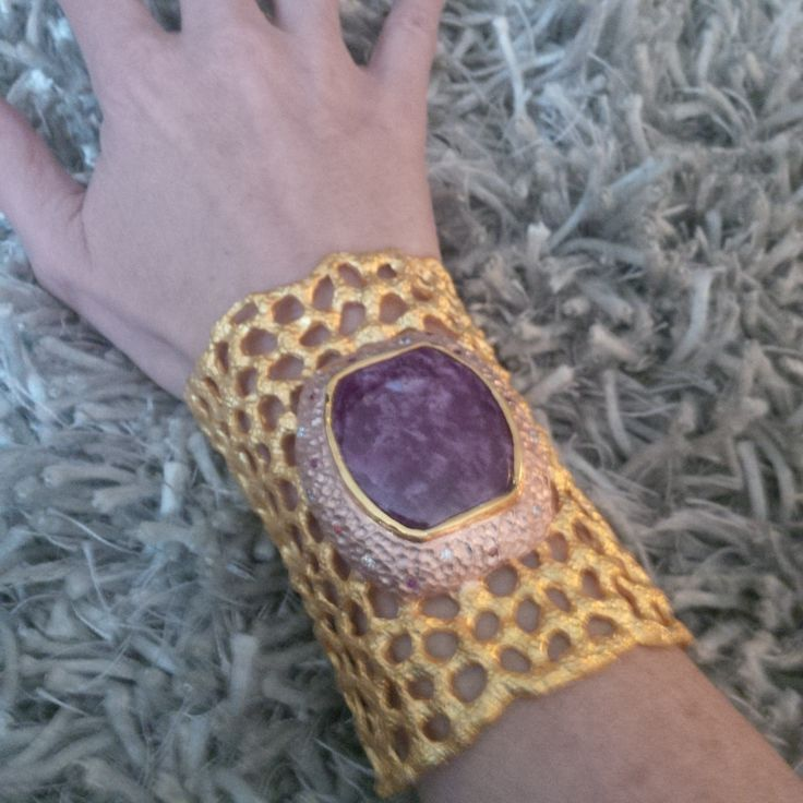 This one-of-a-kind, hand-made, gold plated sterling silver cuff features a large cabochon Sugilite. The collar around the centre stone is pink gold and features Diamonds and Burmese Rubies.