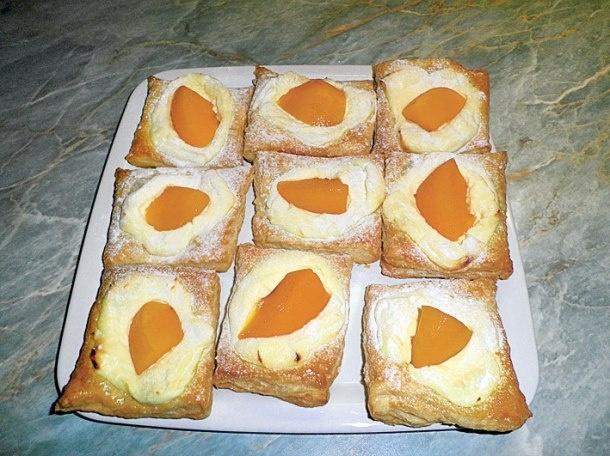 2 měkký plnotučný tvaroh   1 vanilkový pudink   1 vanilkový cukr   na dochucení cukr   1 listové těsto   1 velký broskvový kompot   1 vejce     1.Tvaroh rozmícháme s pudinkovým práškem, vanilkovým cukrem a dosladíme podle chuti.  2.Těsto rozválíme a rozdělíme na čtverečky zhruba 8 x 8 cm. Na plech vyložený pečicím papírem čtverečky rovnou přendáme. Pomažeme je rozšlehaným vejcem. Na každý čtvereček následně naneseme tvaroh a asi čtvrtku broskve. Pečeme v troubě vyhřáté na 180 °C dozlatova.