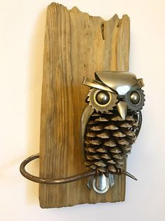 Owl made from upcycled utensils, scrap metal and a pine cone mounted on reclaimed wood. Height: 11 Width: 6 Depth: 3.5