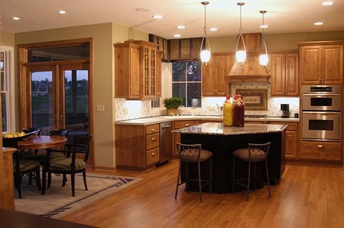 Eclectic eat-in kitchen with stainless steel appliances, natural wood trim, granite counter tops, island seating, hickory kitchen cabinetry with contrasting black lacquered island, wood flooring, pendant and recessed lighting