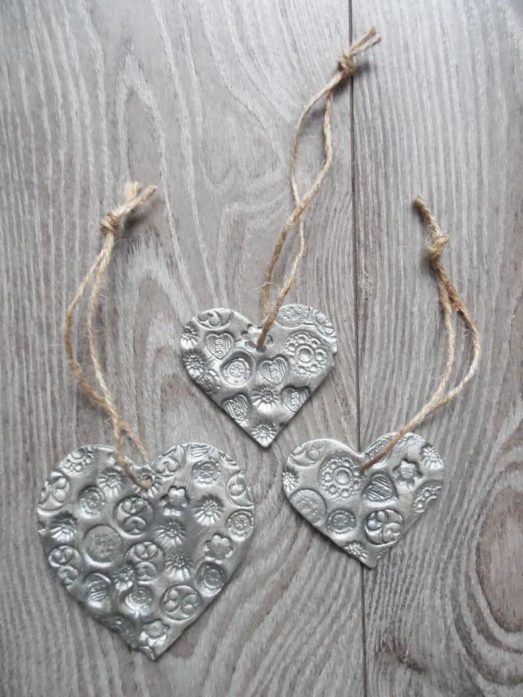 Hangers van zelfdrogende klei gemaakt met afdrukken van knopen..