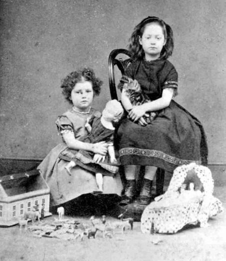 Черно-белая фотография сестренок в игровой комнате. Маленькие барышни в винтажных платьях с серьезными лицами сидят на стульчиках в окружении любимых игрушек - маленькой конюшни, кукольной мебели.