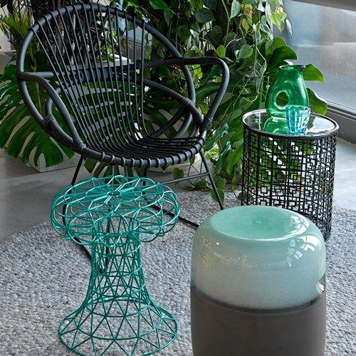 La sedia della Pols Potten è realizzata in rattan nero e denota uno spirito retrò ed elegante, con una seduta leggera e comoda e i braccioli e lo schienale formati da tre canne intrecciate per creare motivi geometrici. La struttura è in nichel.