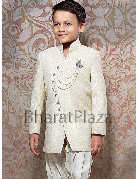 Magnificent cream color angrakha pattern jacquard indo western sherwani is beautified with decorative brooch, shiny buttons and attractive piping on front panel will give smart look your little master. Comes with matching breeches.
