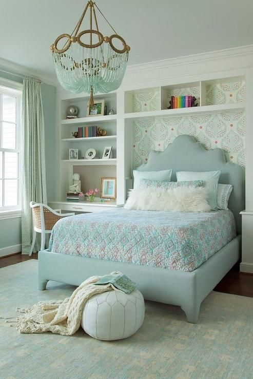 Blue and gray girl's bedroom features a turquoise blue beaded chandelier, Ro Sham Beaux Fiona Chandelier, hanging over a gray upholstered bed dressed in pink and blue bedding and a white sheepskin lumbar pillow lining an accent wall clad in Galbraith & Paul Lotus Wallpaper situated next to a built in bookcase and desk paired with a cane chair.
