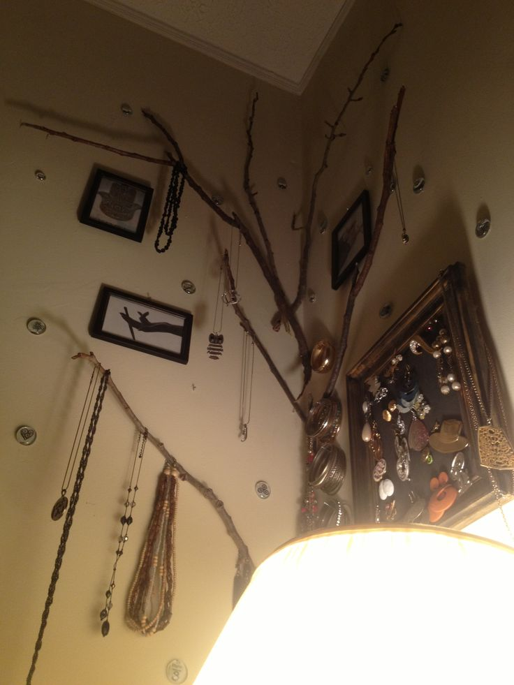 Corner of room, tree, gems, pictures and jewelry on the wall.