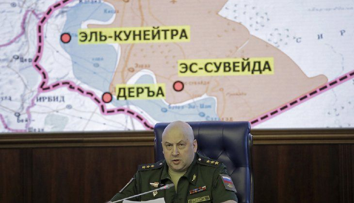 Commander of the Russian forces in Syria speaks with a map of Syria projected on the screen in the back. Russia could begin deploying military police to security zones in Syria after the zones are finalized in two to three weeks, the country's TASS news service reported Tuesday. (AP Photo/Pavel Golovkin)