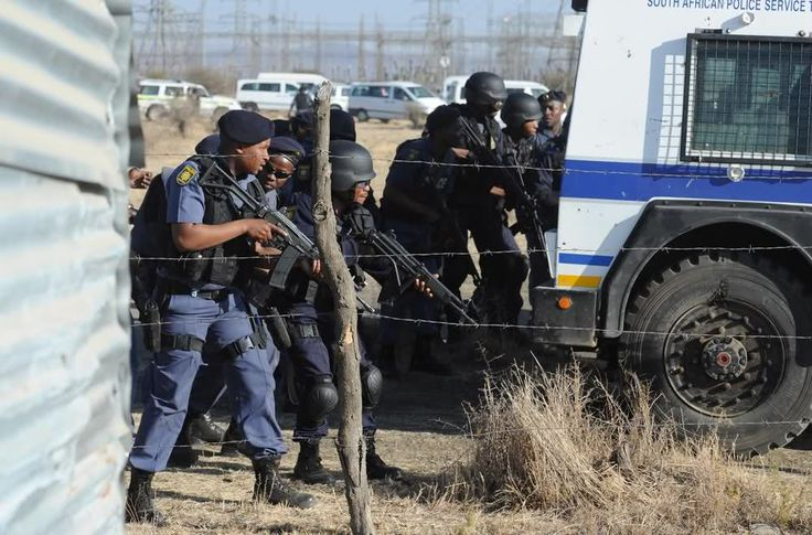 Marikana: A year on | Police look on as striking mineworkers approach.