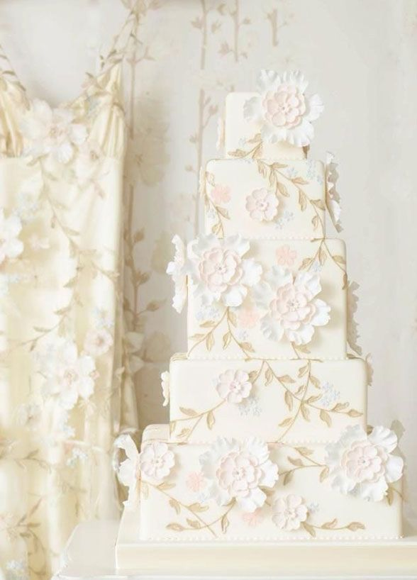 A beautiful white floral cake is detailed in the exact design of the bride's Claire Pettibone wedding gown.