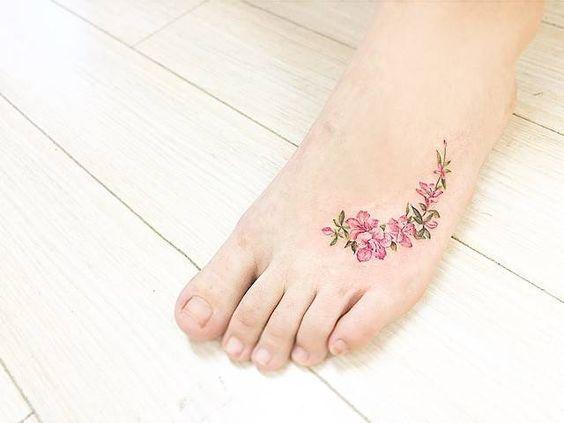 Tatuajes de varias flores de manzana en el empeine del pie izquierdo. Artista tatuador: Banul