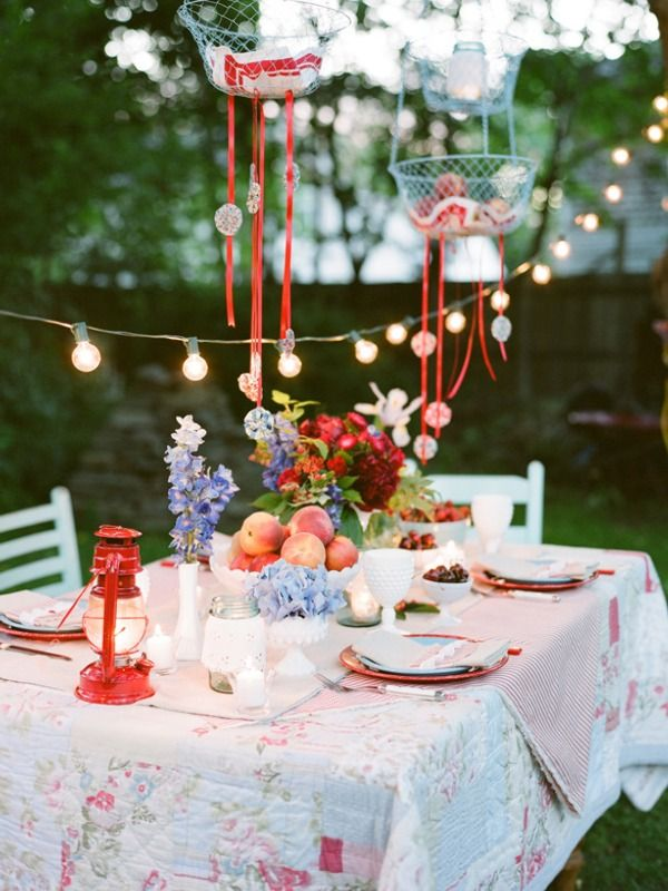Summer garden party. Is that table cloth quilted? I love it. I'd fill those hanging baskets with flowers and fairy lights though.