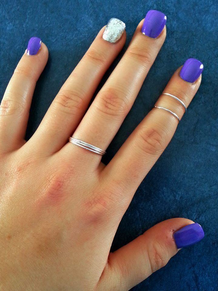 Purple and sparkle nails. Rings.