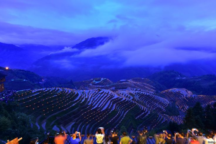 People take pictures of thousands of torches placed in terraced fields during a local festival praying for good harvest at Guilin, Guangxi Zhuang Autonomous Region, China.