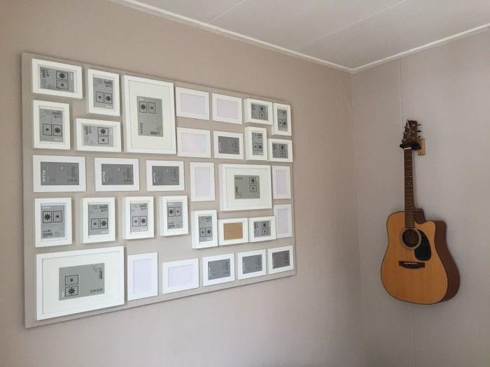 Fotocollage van 33 fotolijsten op een plaat van 140 cm x 100 cm. De plaat zweeft als het ware aan de muur en i.p.v. 33 gaten, zitten er maar 4 gaten in de muur.