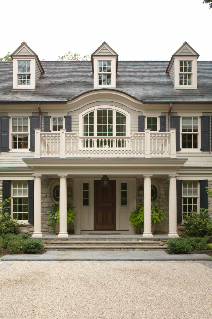 The eyebrow on the roof was used to soften yet distinguish the entrance. Though the exterior details are modest, more emphasis was placed on the entry porch with a decorative balustrade and fluted columns, with the curved roof above.
