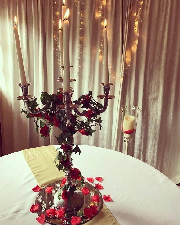 A Beauty & The Beast inspired candelabra centrepiece with red roses, perfect for your wedding or party.  Available to hire from Make It Special Events