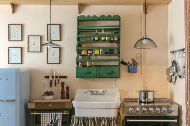 In the kitchen, retro touches such as a Smeg refrigerator and a burlap skirted farmhouse sink balance out the modern stainless steel range. RELATED: 11 Ways to Add Color to Your Kitchen