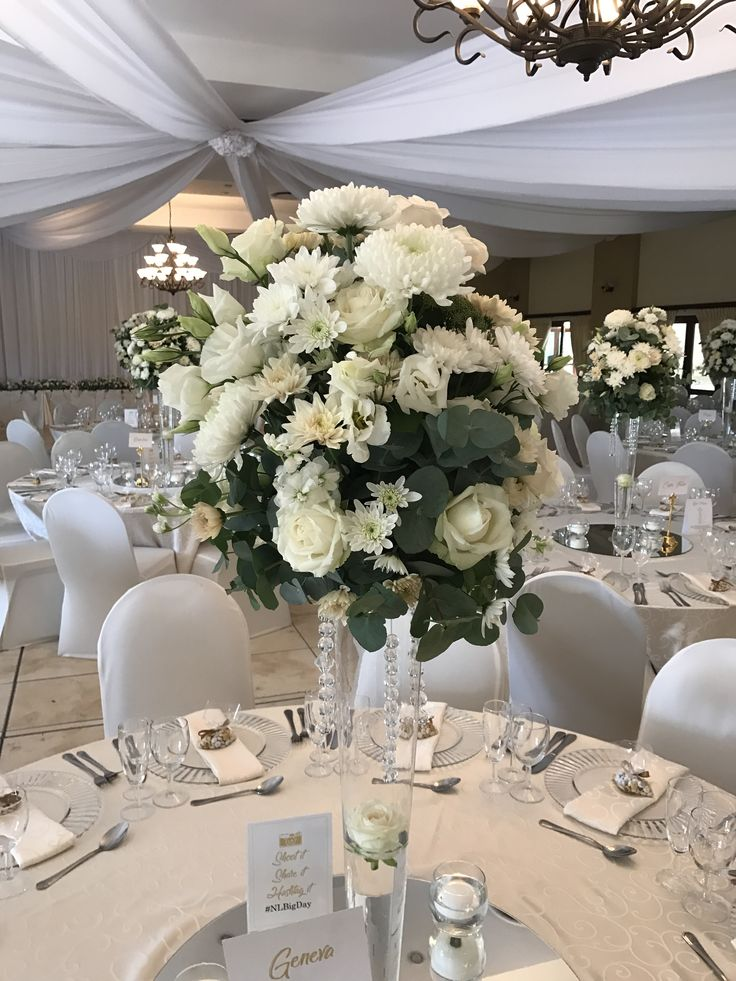 A dramatic tall centerpiece with white & cream flowers by Bliss Floral Creations