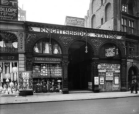 Exterior view of the original entrance to Knightsbridge Underground Station, between shop frontages at 29 and 31 Brompton Road. This station was built in 1906 as part of the Great Northern Piccadilly and Brompton Railway, and later became part of London's tube network. This photograph was commissioned by the Leeds Fireclay Co, formerly known as Burmantofts Co, who specialised in architectural ceramics and who provided the decorative glazed terracotta for the station's facade.