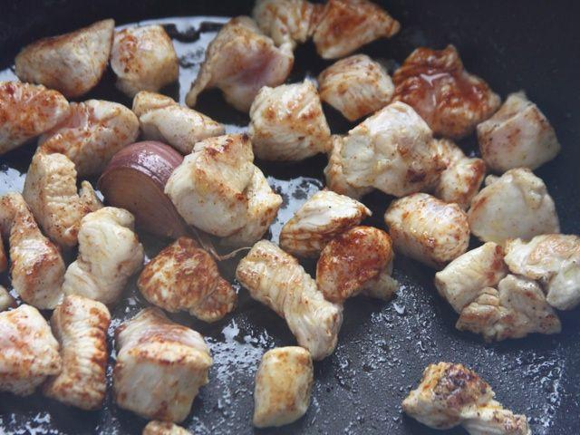 QUESADILLAS CON POLLO 2/5 - Dividete a dadini il petto di pollo. Fate scaldare 2 cucchiai di olio in una padella antiaderente con l'aglio leggermente schiacciato. Unite il pollo, cospargetelo con la paprika e insaporitelo con sale e pepe. Fatelo dorare rapidamente da tutti i lati quindi toglietelo dalla padella e tenetelo da parte.