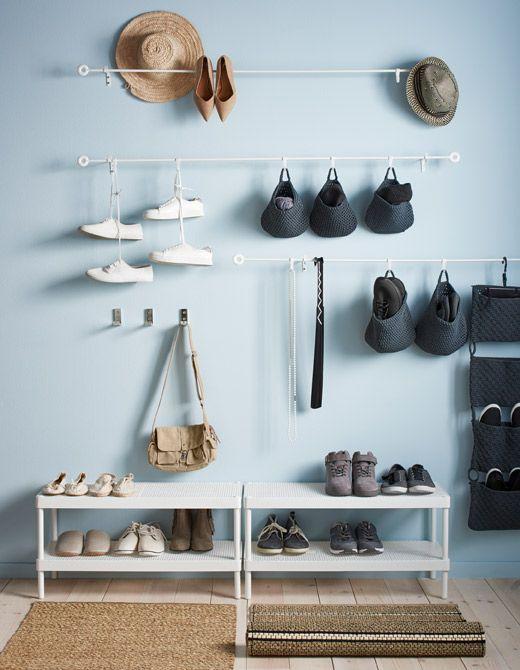 Boven twee schoenenrekken hangen witte roedes met hangmanden en schoenen aan