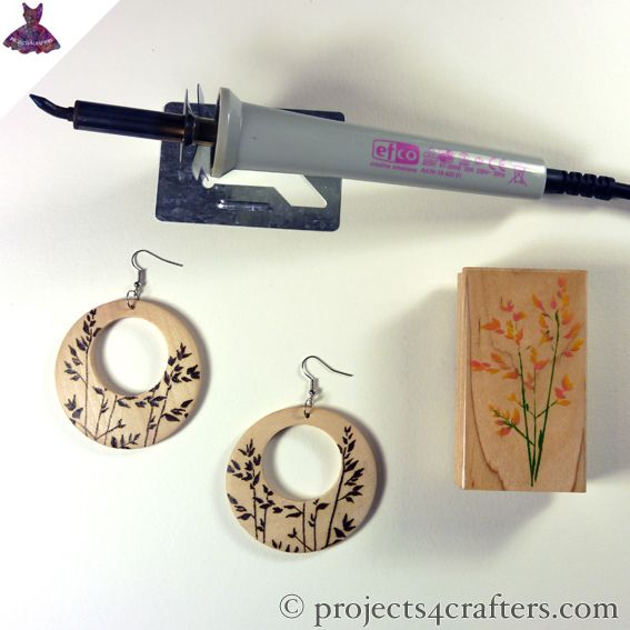 These wooden earrings are from Pébéo. The rubber stamp was used for inspiration and Efco's pyrography tool was used to burn the design into them. They were then varnished for protection.