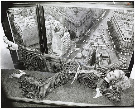 Model, lying on a window sill at the Hotel Concorde-Lafayette, Paris, with  a view of the city behind her; and wearing a small polka dot print pajama  with f...