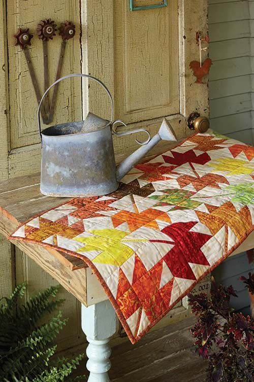 Choose a collection of batiks in fall hues to make this easy table runner. This table runner quilt pattern warms up any home as temperatures start to plummet. Fall in in the air!