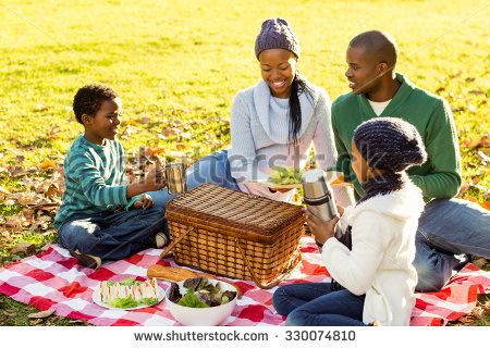 Young smiling family doing a picnic on an autumns day - stock photo