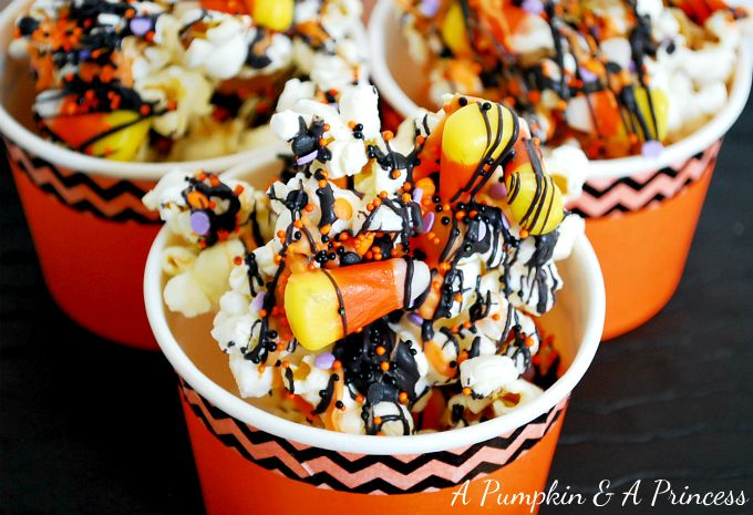 Halloween Popcorn - Popped corn, melted Wilton Candy Melts, Candy Corn & various sprinkles. Super easy to make. Recipe from A Pumpkin & A Princess.