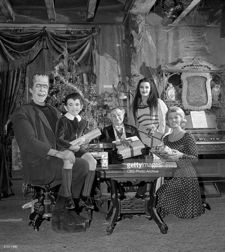 The cast of the CBS television situation comedy 'The Munsters' including (left to right) American actor and children's book author Fred Gwynne (1926 - 1993) (as Herman Munster), child actor Butch Patrick (as Eddie Munster), actor and later politician Al Lewis (as Grandpa), Canadian actress Yvonne de Carlo (as Lily Munster), and American debutante and actress Pat Priest (as Marilyn), sit at a table and hold Christmas presents in a cobwebbed living room complete with Christmas tree and organ…