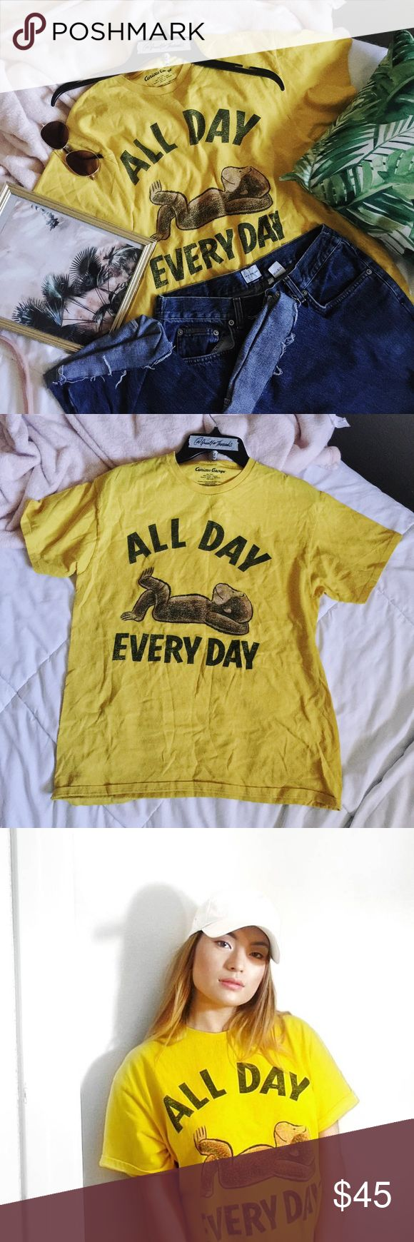 "Curious George•All Day Everyday Graphic Yellow Tee Curious George•All Day Everyday Graphic Yellow Tee  Adorable curious George cotton t shirt.  Hardly worn, size Large--can fit a size medium as an oversized casual look as well Cute Yellow color--varies depending on lighting  Approximate measurements: Length: 27"" Bust: 21"" Armpit to armpit curious geroge Tops Tees - Short Sleeve"