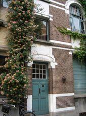 Voorgevel - Klimmende (bloemen)plant naast de voordeur. Wilde Kamperfoelie. Welkom!