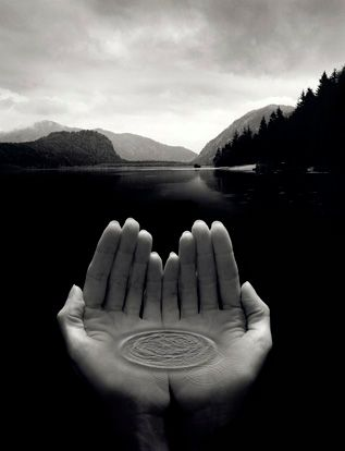 Title: Untitled Date: 2003 Photographer: Jerry Uelsmann Jerry Uelsmann's work is all about the natural earth. He like to show how natural it is and how must of a mystery it is. In this photo he is showing how close it is and that the earth is in our hands. In the hands is a ripple that the lake would make if a stone was thrown in the water, so it looks like the hand are holding the water and holding the earth or environment.