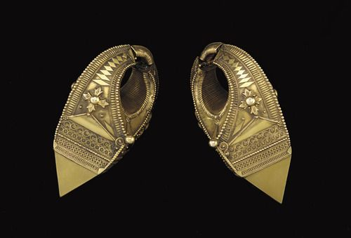 Pair of Kerala earrings    ca. 1880        gallery note: Hollow earrings such as these, in which a loop links a pyramidal form that resembles a faceted stone, are constructed of soldered sheet metal. They are elaborately decorated with applied bead and wire designs of floral, diamond, linear, spiral, and other geometrical forms. Such earrings are typically worn by Muslim women in the southern state of Kerala along the west coast of India.