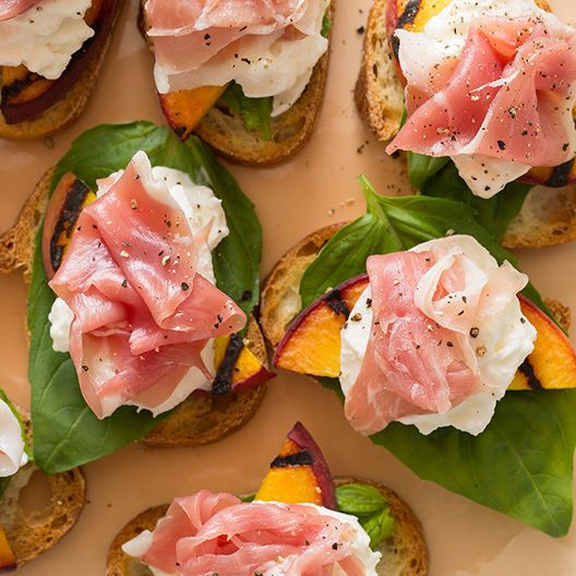 A really easy appetizer recipe for Grilled Peach and Burrata Crostini. We layer burrata, basil, grilled peaches, and proscuitto on a crostini. | via Spoon Fork Bacon