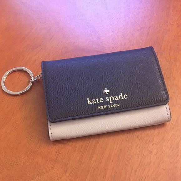 Kate spade small ID wallet with keychain. NWOT Kate Spade NWOT Small ID wallet. Has inside zip pocket plus other pockets to hold cards. Exterior clear pocket for ID and handy key ring! Never worn! kate spade Bags Wallets