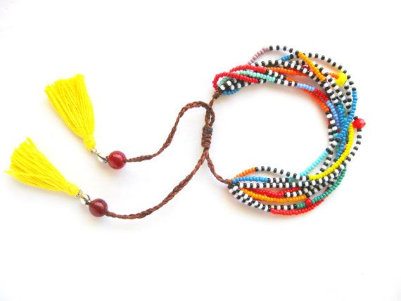 Tribal Style Multi Strand African Seed Bead Bracelet. The bracelet features eight beaded strands which are made from czech glass seed beads, jade stones and yellow cotton tassels. Size: Adjustable to any size  If you have any question about the item, please feel free to message me.