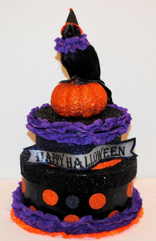 """Halloween will soon be upon us so what better way to get a head start on this """"Frightening"""" Holiday than with a centerpiece sure to bring """"oohs and ahhs"""" and guaranteed to brings smiles. This is a 2 tier centerpiece, sparkling in black glitter, orange and black polka dots, purple and orange crepe paper trim with a crow on top. Tier 1 is 9"""" wide, Tier 2 is 6"""" wide and it stands 15 1/2"""" tall. #Halloween #Halloweendecorations #Crowcenterpieces #handmadehalloween #handmadehalloweenboxes"""
