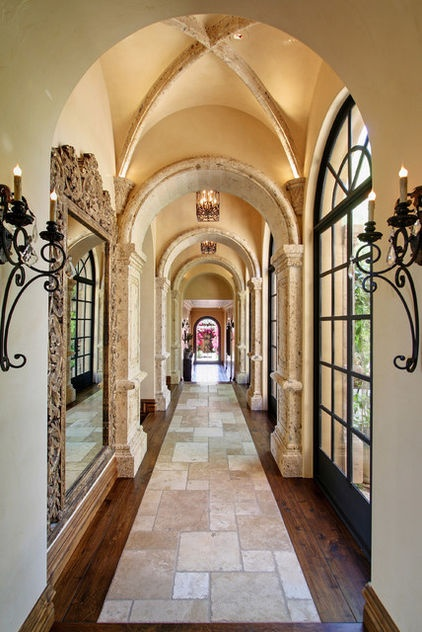 The groin vaults in the ceiling are a traditional Spanish colonial touch, as are the wrought iron doors and sconces. Travertine forms a unique stone runner down the middle of the walnut floors