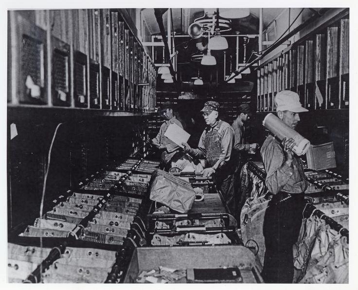 This is an image of Railway Post Office clerks at work sorting mail inside the tight quarters of an RPO car.