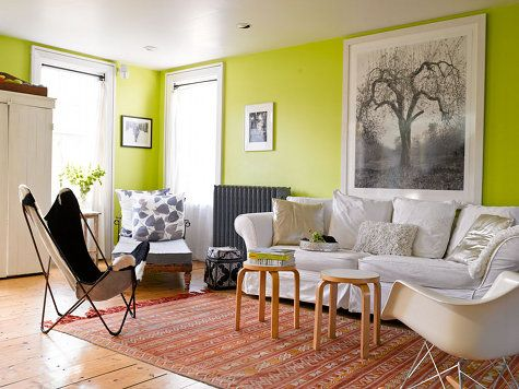 bright kiwi green living room white sofa colorful rug two stools as coffee table