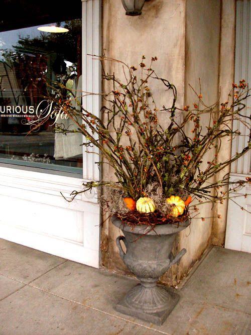 front door pot with twigs and pumpkin