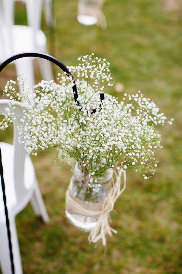 The ceremony aisle will be marked with blue mason jars filled with white baby's breath hanging from shepherd's hooks.