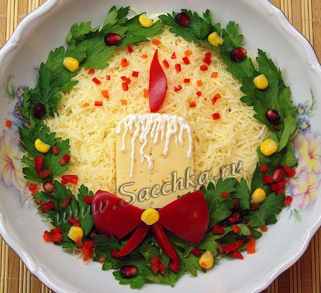 Как украсить новогодний салат свечой из сыра и веночком из зелени.